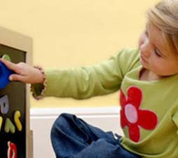 autistic girl touching magnetic letters