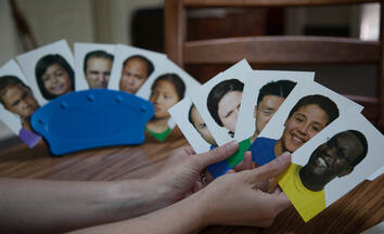 person-holding-5-emotion-cards-and-5-cards-in-holder-in-the-background