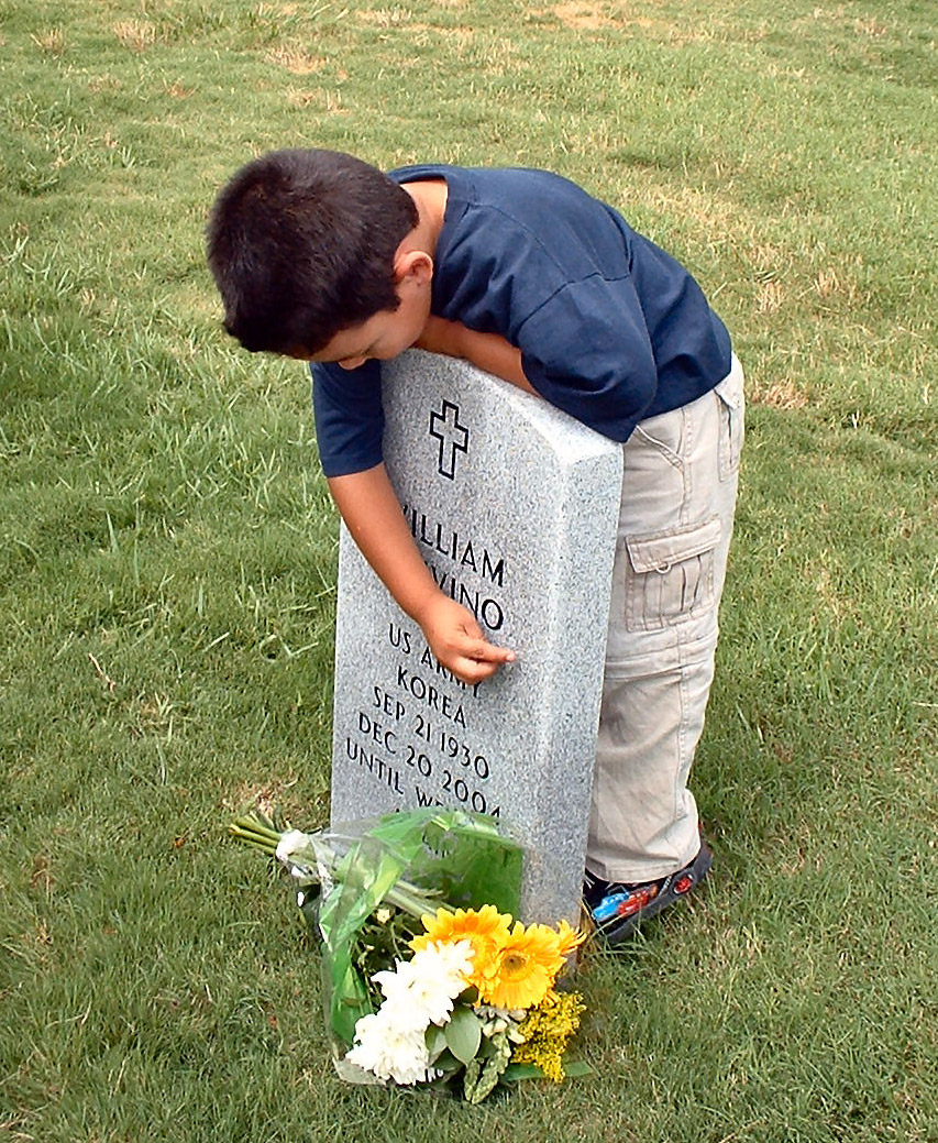 boy-embracing-grave-with-fresh-flowers