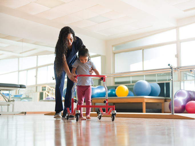 A physical therapist helping a little girl with autism to walk with a wheeled walking frame