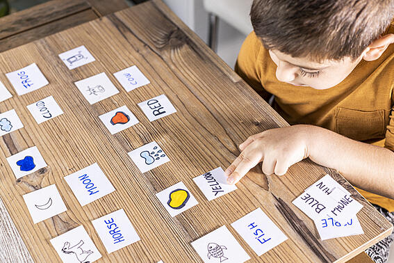 Boy with autism playing with cards of words and pictures