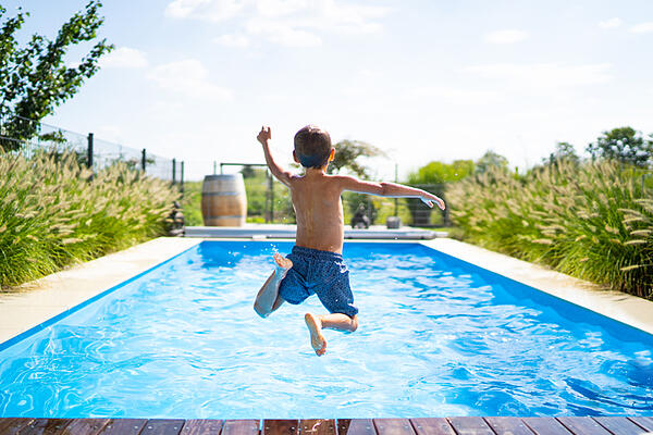 boy with autism jumping into pool developing gross motor skills
