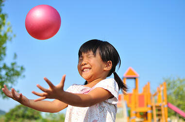 girl with autism catching ball developing gross motor skills