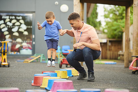 Daycare teacher with child with autism in playground