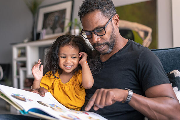 Father on the couch at home reading a storybook to his preschool age daughter with autism