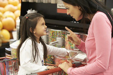 Girl With Autism Having Argument With Mother At Candy Counter In Supermarket