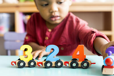 Little boy with autism playing mathematics wooden toy at daycare