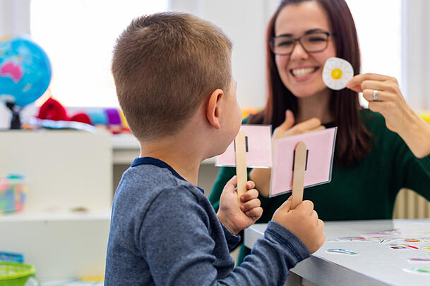 Preschooler with autism practicing correct pronunciation with a female speech therapist