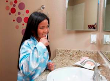 girl with autism brushing her teeth in the bathroom