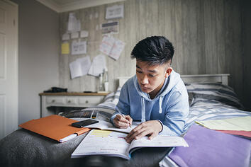Teenage boy with autism lying on his bed while concentrating on homework