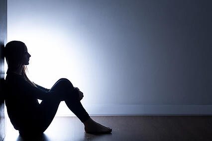 Teenager with autism depression sitting alone in dark room
