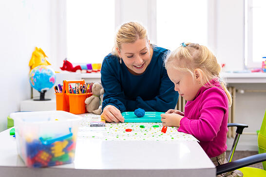 Toddler girl with autism in child occupational therapy session doing sensory playful exercises with her therapist.