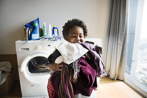 Young boy with autism doing laundry at home