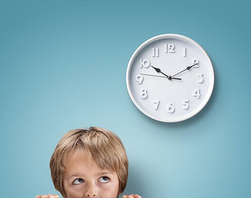 Young boy with autism looking up at a clock
