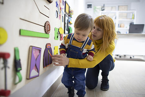 Young mother and her son with autism playing with wooden interactive board at psychotherapy office.