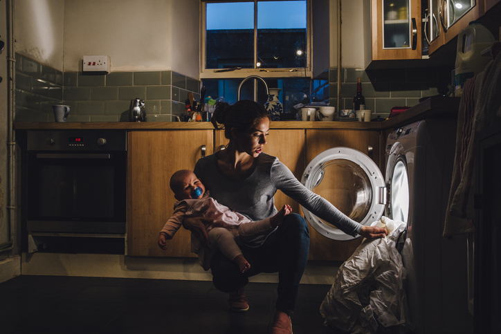 Young mother with children with autism is holding her crying baby daughter on her hip while trying to load the washing machine