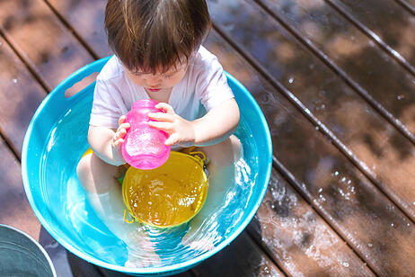 Young toddler boy with autism playing with water outside