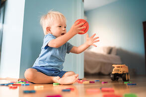 baby boy having fun at home playing with ball