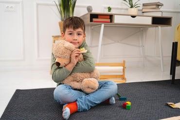 boy embracing teddy bear as a reward
