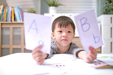 boy with autism holding flashcards learning phonological awareness