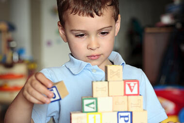 boy with autism playing with blocks