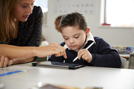 boy with disabilities working on a tablet receiving extra help from teacher