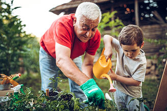 boy-helping-grandfather-with-gardening