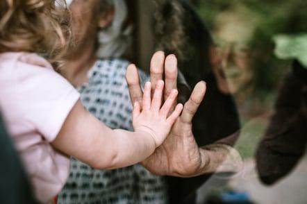 child visiting senior parents but observing social distancing