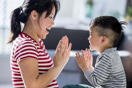 child with autism clapping and repeating pattern with his mother