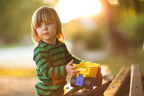 child with autism playing with toy truck