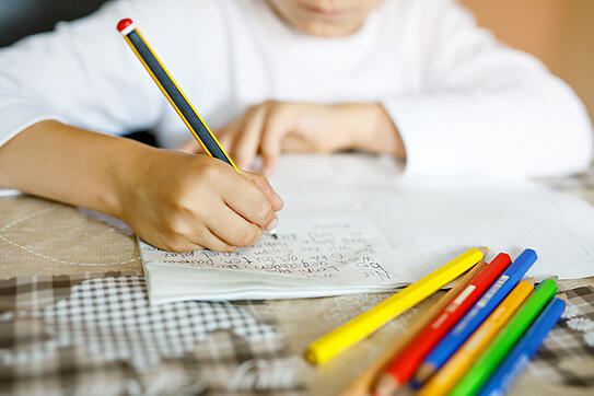 child with autism practicing writing words with different colored pencils