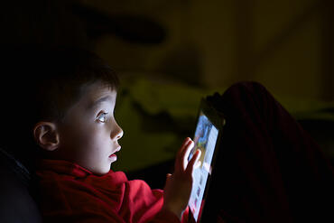 child with autism using tablet in the night