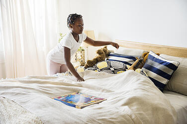 child-making-her-bed