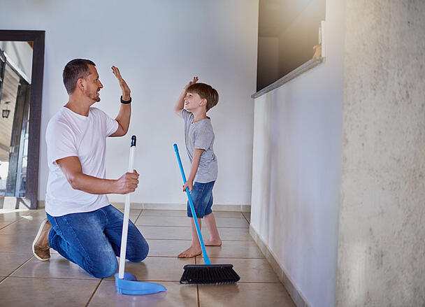 father and his little son with autism high fiving each other while sweeping the floor at home