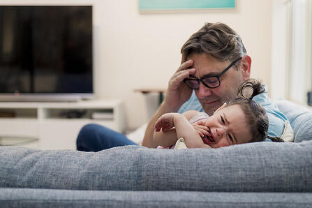 father looks in despair as his daughter with autism gets upset