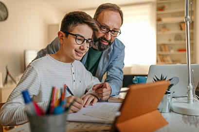 father-helping-son-with-autism-online-learning