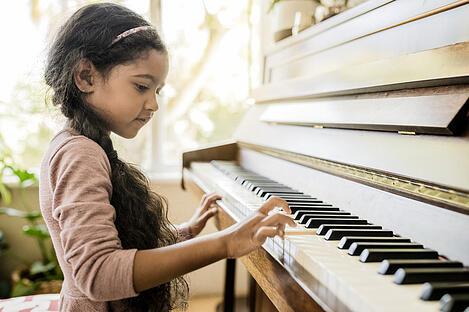 gifted girl with autism playing the piano