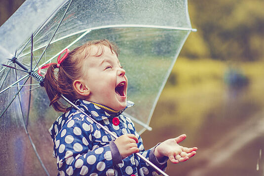 girl with autism playing in the rain with umbrella