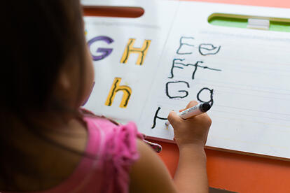 girl with autism practicing writing letters
