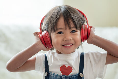 girl with autism wearing noise canceling headphones for sensory