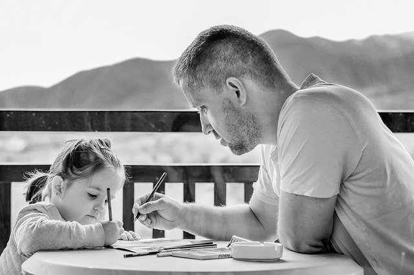 dad writing with autistic daughter during coronavirus