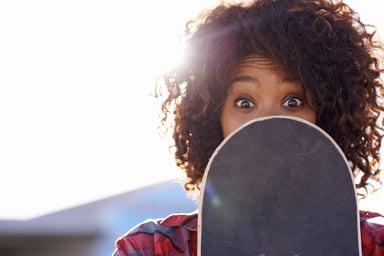 girl-hiding-behind-skateboard