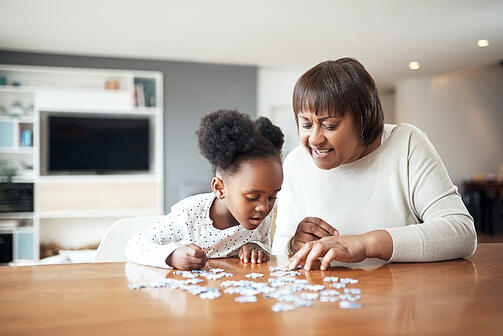 little girl with autism building a puzzle with her grandmother at home