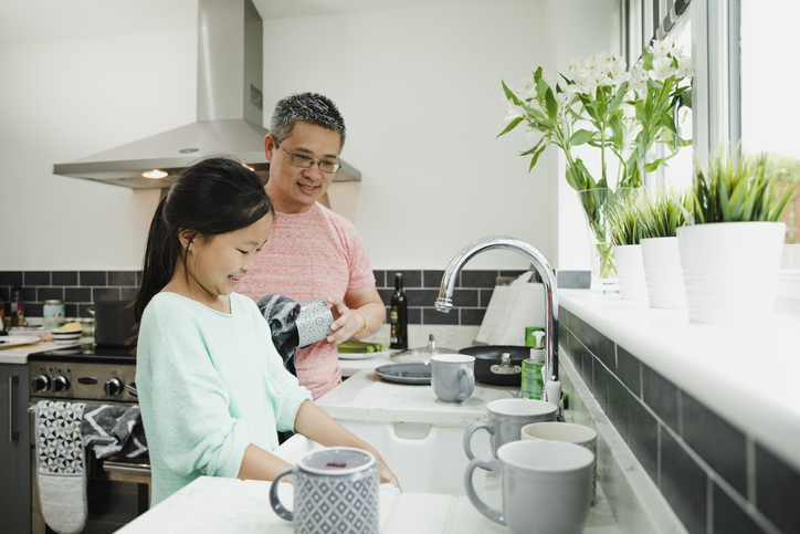 little girl with autism in the kitchen washing dishes with her father