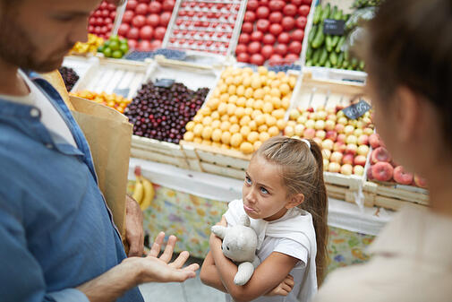 little girl with autism refusing to cooperate with parents at farmers market