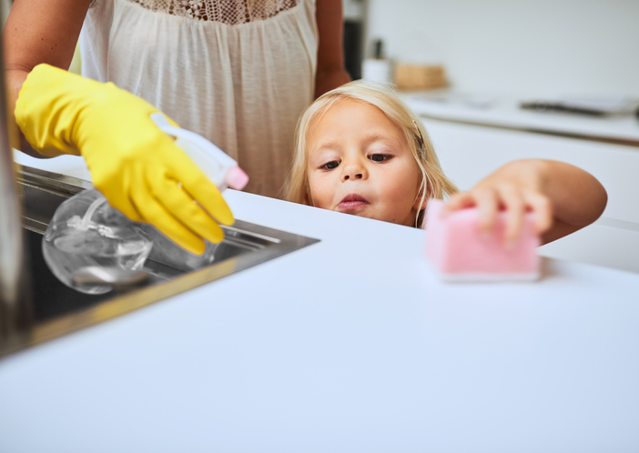 mother and her little daughter with autism cleaning a kitchen surface together at home