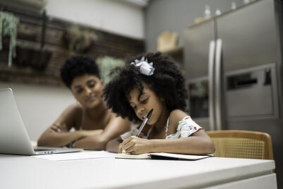 mother helping daughter with autism learn to write