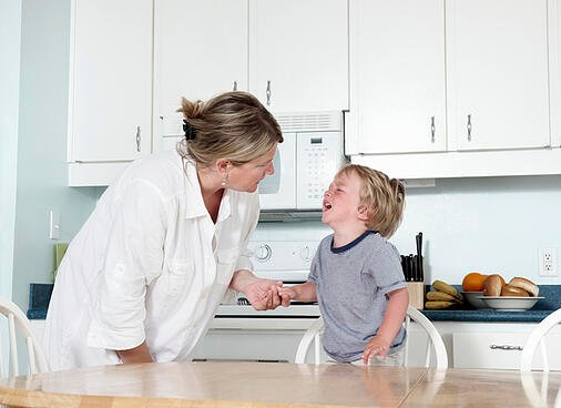mother trying to calm her crying toddler with autism at home in their kitchen
