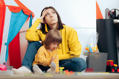 overwhelmed mom of child with autism thinking concerned being stressed and wondering about daily problems