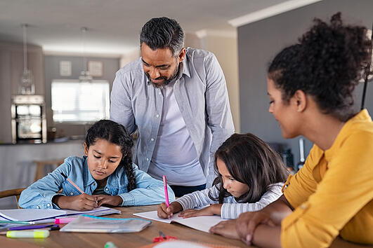 parents helping children with autism with their homework at home